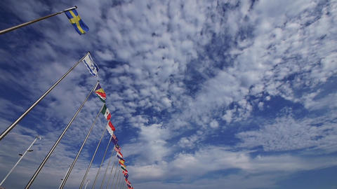 Many national flags fluttering in the wind against clouds... Stock Video Footage
