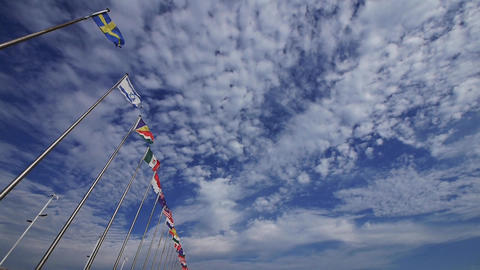 Many national flags fluttering in the wind against clouds background Animation