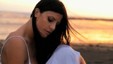 Beautiful woman in magic sunset light on the beach thinking in love Animation