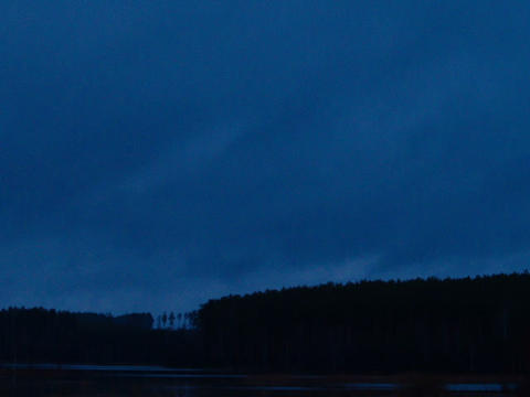 Above the lake rain. Night comes. Time Lapse Footage