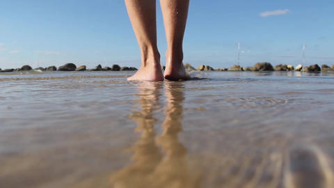 Women walks on the beach leaving footprints in the Footage