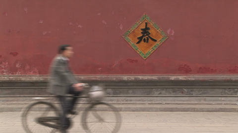Bike Riding past a Red Wall in Beijing, China Footage