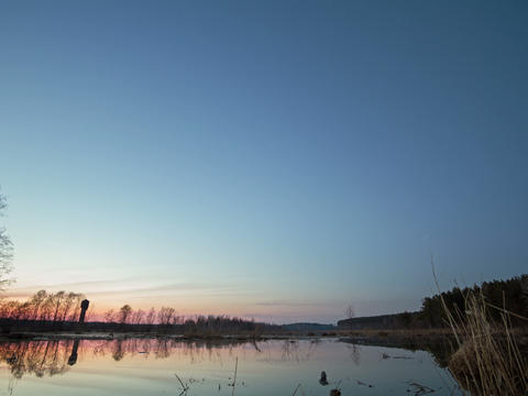 Sunset and starry sky reflected in lake. Star trac Footage