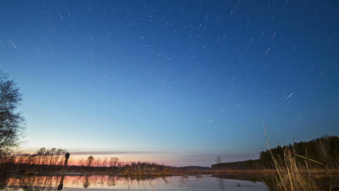 Sunset and starry sky reflected in lake. Star trac Stock Video Footage