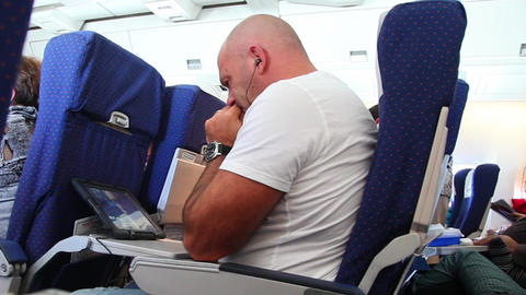 Man with tablet computer sitting in the plane Stock Video Footage