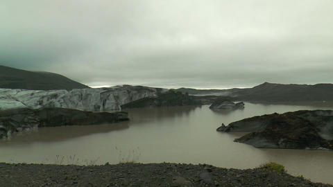 Icebergs in glacial lake covered with lava ash Stock Video Footage