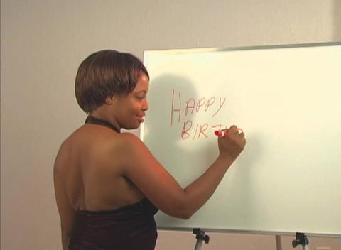 "Sexy woman writes ""Happy Birthday Handsome"" on a white board Footage"