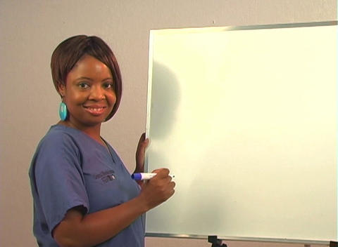 "Beautiful Nurse Writes ""Hemorrhoidectomy"" on a White Board Stock Video Footage"
