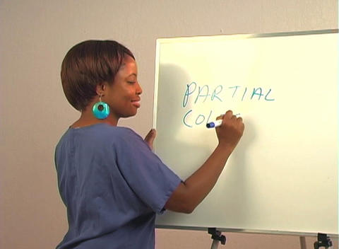 "Beautiful Nurse Writes ""Partial Colectomy"" on a White Board Stock Video Footage"