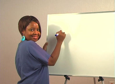 "Beautiful Nurse Writes ""Tonsillectomy"" on a White Board Stock Video Footage"