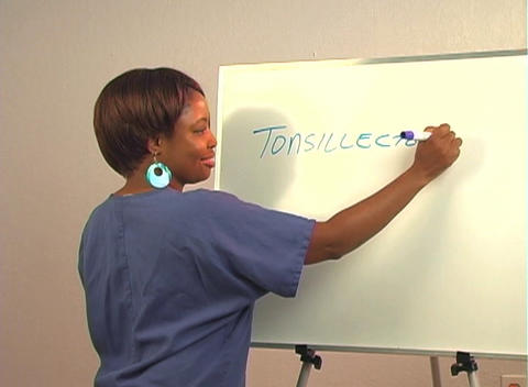 "Beautiful Nurse Writes ""Tonsillectomy"" on a White Board Footage"