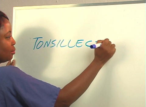 "Beautiful Nurse Writes ""Tonsillectomy"" on a White Board (close-up) Footage"