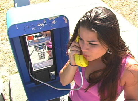 Beautiful Brunette Talks on a Pay Phone (sequence) Footage