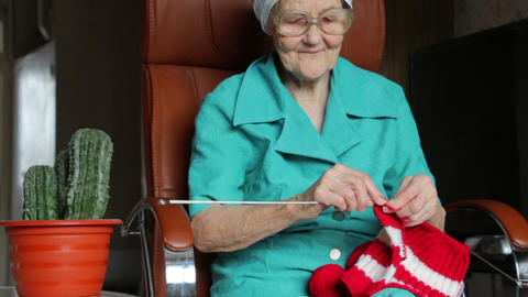 old woman sitting on chair and knitting Stock Video Footage