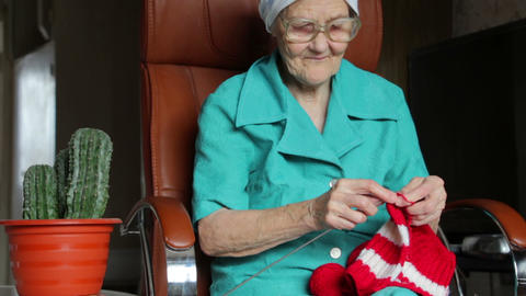 old woman sitting on chair and knitting Footage