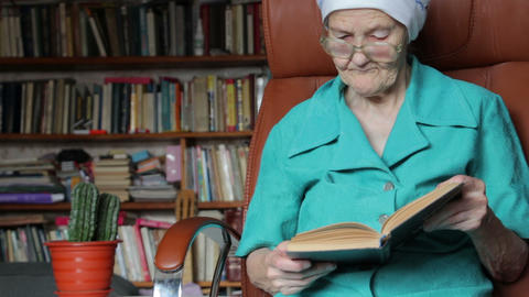 old woman sitting on chair and reading book Stock Video Footage