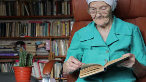 old woman sitting on chair and reading book Footage