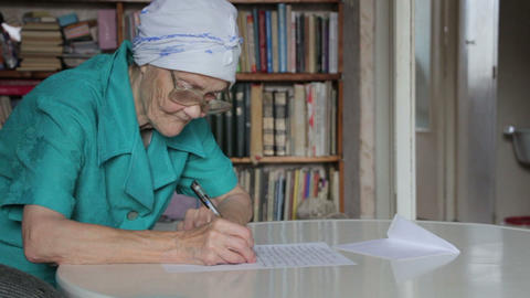 old woman writing letter then take off glasses Footage