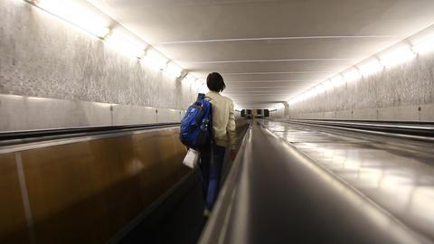 Woman riding an escalator Stock Video Footage