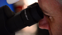 Man Analyzing With A Microscope stock footage