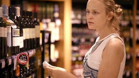 Woman shopping for alcohol in a bottle store Footage