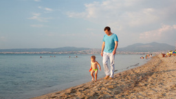 Father and his small son walking on the beach Stock Video Footage