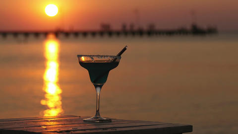 Tropical cocktail overlooking a sunset ocean Stock Video Footage