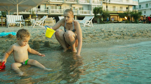 Little boy and his mother playing on the beach Stock Video Footage