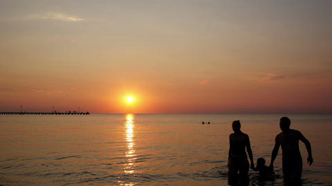 Young family on the beach under a colourful sunset Stock Video Footage