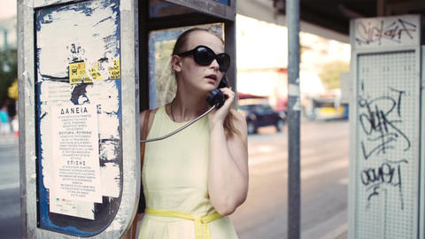 Woman chatting on a public telephone Stock Video Footage