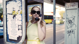 Woman chatting on a public telephone Footage