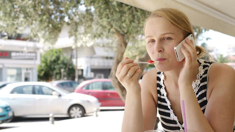 Woman eating refreshments and using a mobile Footage