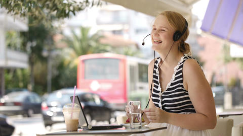 Laughing woman wearing a headset in outdoor cafe Stock Video Footage