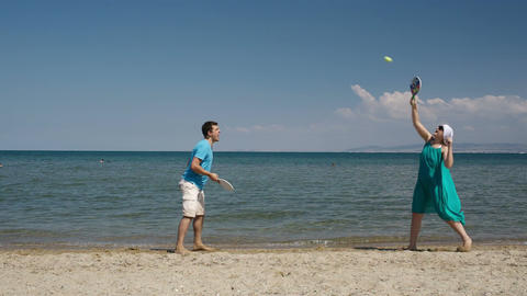 Couple playing bat and ball at the beach Footage