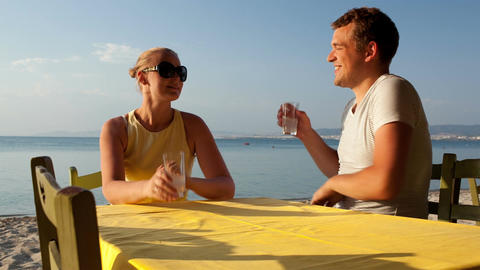 Young couple enjoying drinks at the seaside Stock Video Footage
