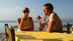 Young couple enjoying drinks at the seaside Footage