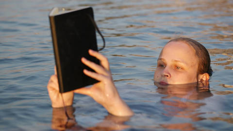 Woman Reading While Floating In The Sea stock footage