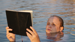 Woman reading while floating in the sea Stock Video Footage