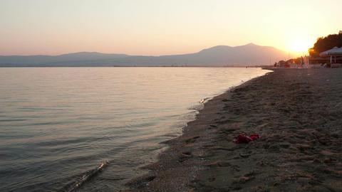 Man running along a beach at sunset Stock Video Footage