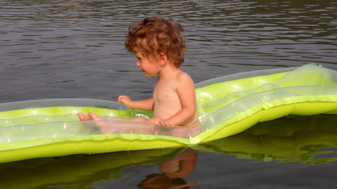 baby bathing in river on inflatable mattress Stock Video Footage