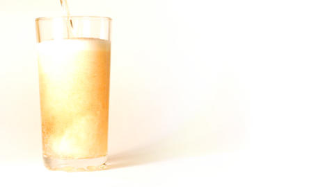 beer is poured into a glass on white background -  Footage