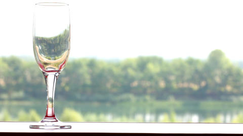 glass filled with red wine on summer landscape bac Stock Video Footage