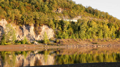 autumn landscape with moving train and river Stock Video Footage