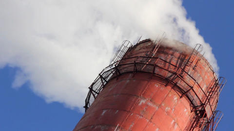 factory chimney with smoke under blue sky Footage