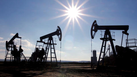 working oil pumps silhouette against sun Stock Video Footage
