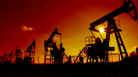 working oil pumps silhouette against sun - timelap Footage