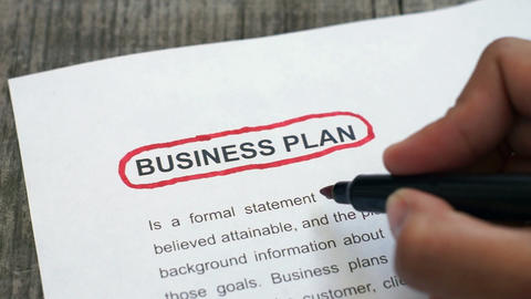 Circling Business Plan with a red marker Footage
