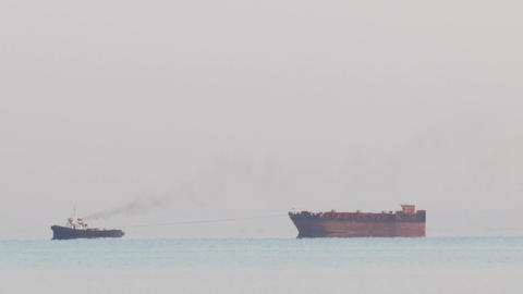 Tugboat tugging a large barge in an overcast day Stock Video Footage