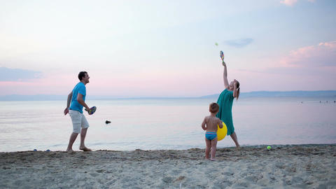 Young family playing tennis at the seaside Stock Video Footage