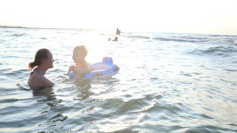 Mother swimming with her little boy in the sea Stock Video Footage